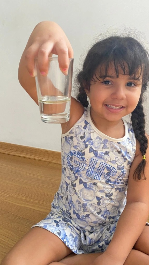Criança segurando copo d'água